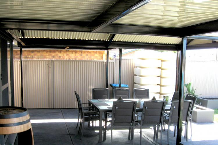 Outdoor entertaining area with verandah, plantar boxes and backyard.