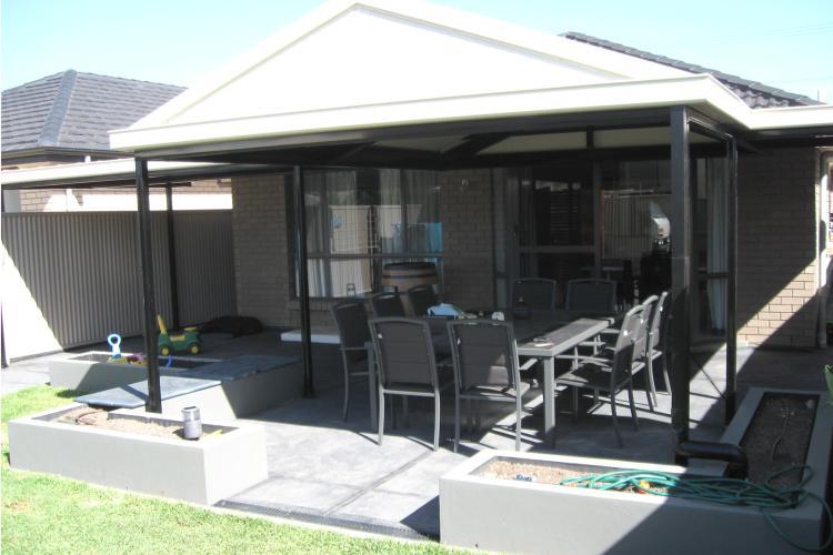 Outdoor entertaining area with verandah, plantar boxes and backyard.